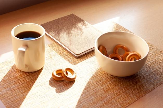 Filiżanka kawy, barankis, notatnik na drewnianym stole. brązowe i białe.