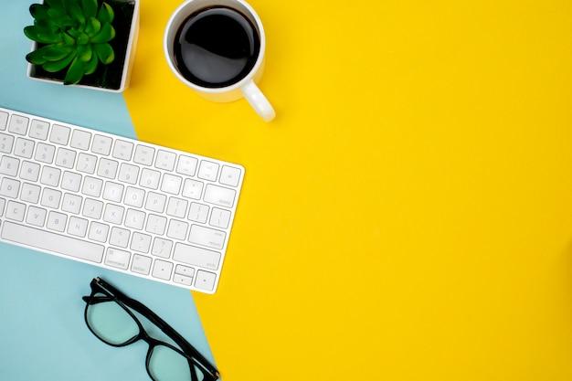 Filiżanka kawy, bezprzewodowa klawiatura i szklanki