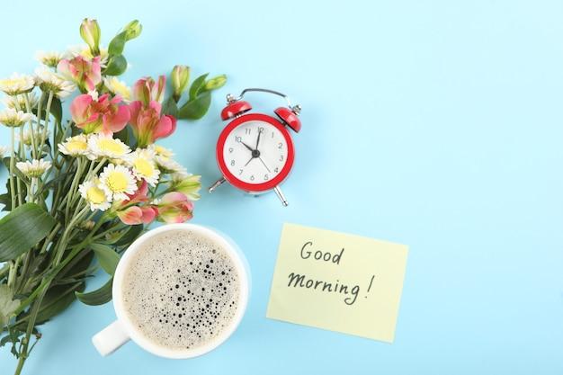 Filiżanka kawy bukiet kwiatów i kartka z napisem dzień dobry