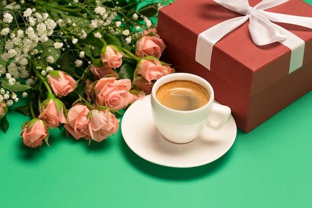 Filiżanka kawy, bukiet róż i czerwone pudełko na zielonym tle