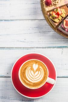 Filiżanka kawy cappiciino i mini surowe ciasteczka.