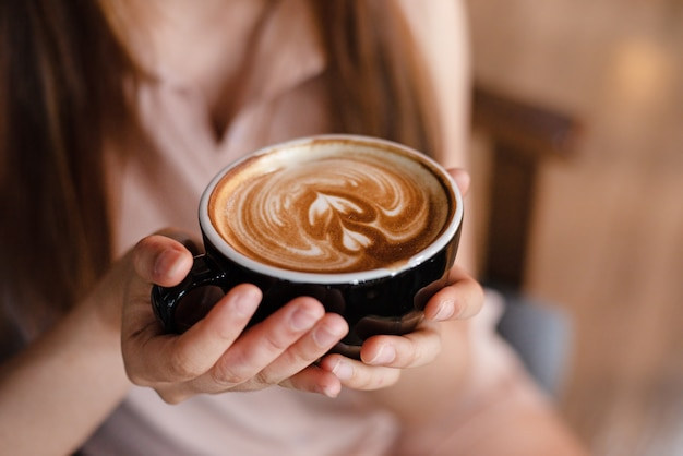 Filiżanka kawy cappuccino w dłoni pani