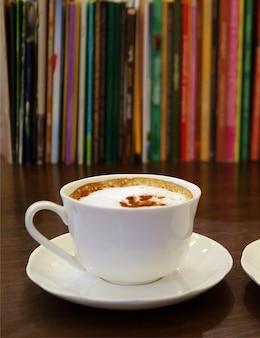 Filiżanka kawy cappuccino z zamazanymi rzędami książek w tle
