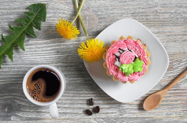 Filiżanka kawy, ciasta i kwiaty na starym drewnianym stole, widok z góry