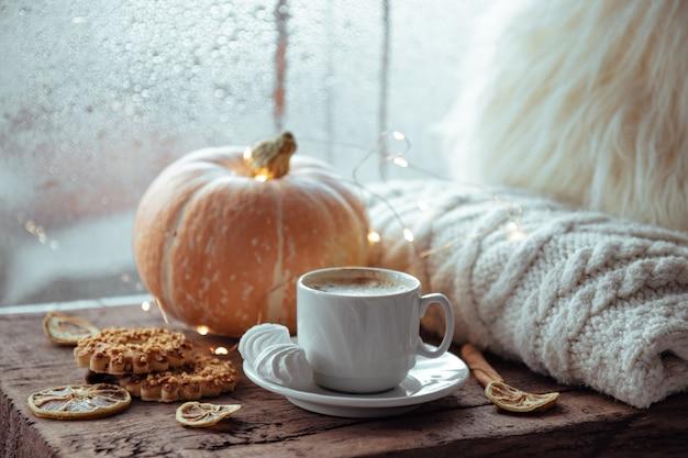 Filiżanka kawy, ciasteczka i dynia na parapecie. koncepcja jesień.