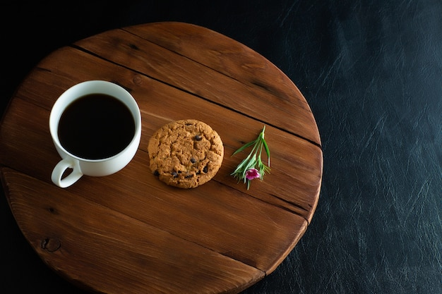 Filiżanka kawy, ciasteczka i mały różowy kwiat na drewnianej tacy