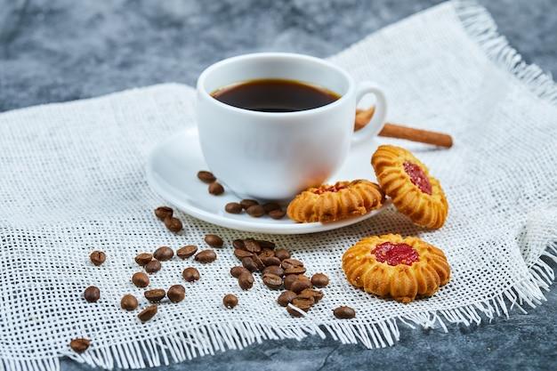 Filiżanka kawy, ciastka, ziarna kawy i cynamon.