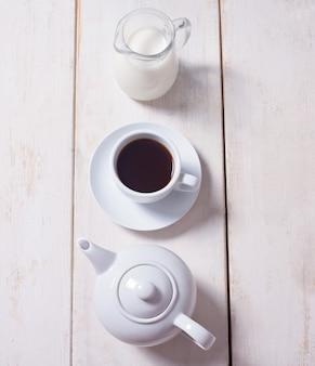 Filiżanka kawy, czajnik i dzbanek z mlekiem w rzędzie
