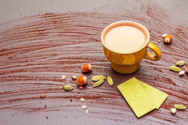 Filiżanka kawy, czekolada z herbatą matcha, orzechy laskowe, proszek kakaowy i kardamon