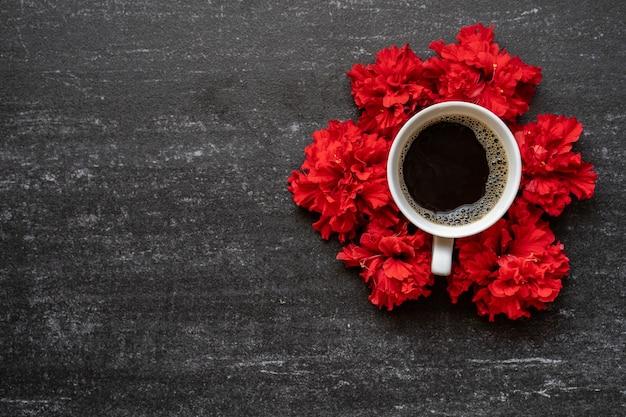 Filiżanka kawy, czerwony kwiat na czarnym stole.