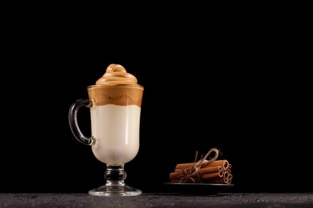 Filiżanka kawy dalgona na ciemnym, mokrym blacie.
