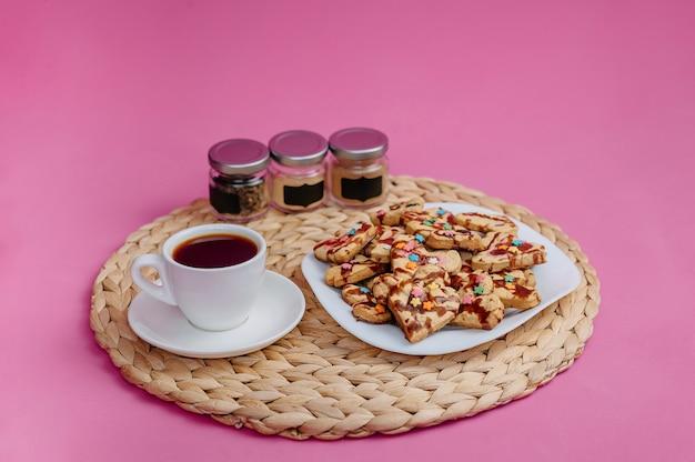 Filiżanka kawy, domowe ciasteczka i naczynia kuchenne na różowym tle.