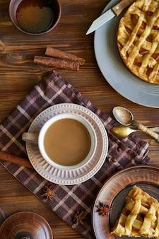 Filiżanka kawy, domowe ciasto brzoskwiniowe, ziarna kawy na drewnianym porannym śniadaniu