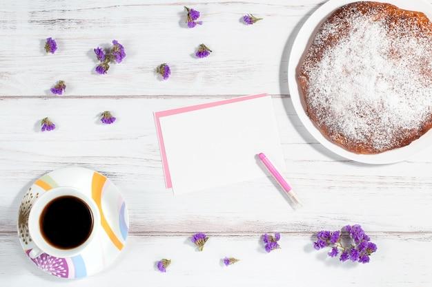 Filiżanka kawy, domowe ciasto, kartka papieru i wiele małych fioletowych kwiatów