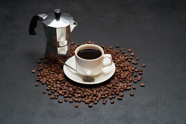 Filiżanka kawy espresso i ekspres do kawy mokka na palonych brązowych ziarnach kawy na betonowym stole