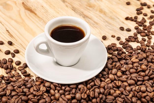Filiżanka kawy espresso i palonej fasoli na drewnianym stole. skopiuj miejsce.
