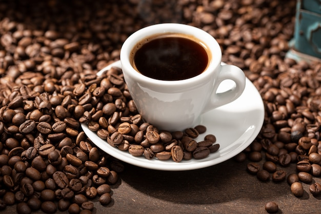 Filiżanka kawy espresso i palonych ziaren. kawa w tle
