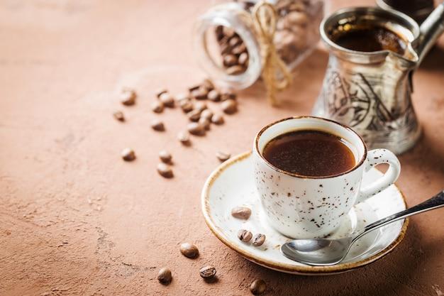 Filiżanka kawy espresso i ziarna kawy na brązowym kamieniu