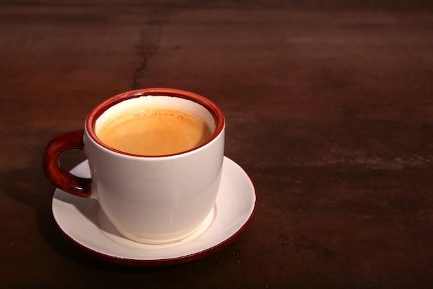 Filiżanka kawy espresso na ciemnej drewnianej powierzchni