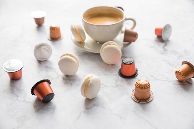 Filiżanka kawy espresso podana z makaronikami i kapsułkami na marmurowym stole.