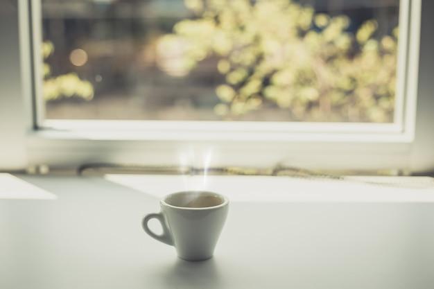 Filiżanka kawy espresso postawiona na stole przy oknie