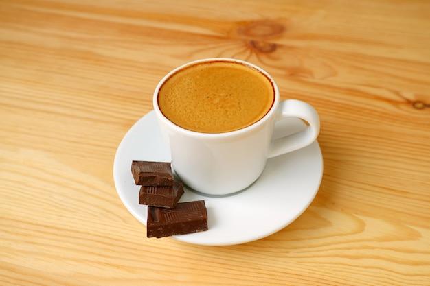 Filiżanka kawy espresso z kostkami ciemnej czekolady na białym tle na drewnianym stole