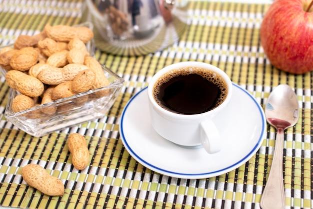 Filiżanka kawy expresso z orzeszkami ziemnymi i owocami