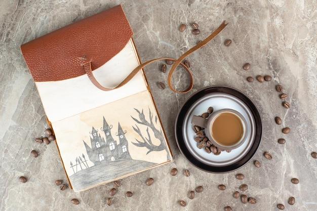 Filiżanka kawy, fasola i notes na marmurowej powierzchni.