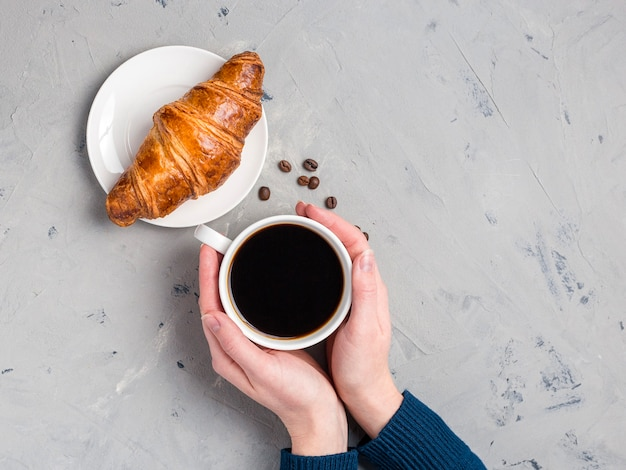 Filiżanka kawy, fasola i rogalik. widok z góry na ręce kobiety trzymając kubek z kawą i świeżym francuskim rogalikiem