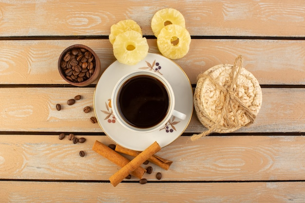 Filiżanka kawy gorąca i mocna z widokiem z góry ze świeżymi brązowymi ziarnami kawy cynamonem i krakersami na kremowym rustykalnym biurku ziarno kawy napój zdjęcie ziarno