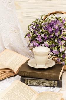 Filiżanka kawy (herbata), książki i bukiet lnu w wiklinowym koszu. w stylu retro, vintage