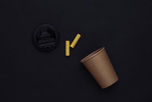 Filiżanka kawy i baterie na czarnym tle. opłata za energię