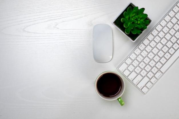 Filiżanka kawy i bezprzewodowa klawiatura z myszą