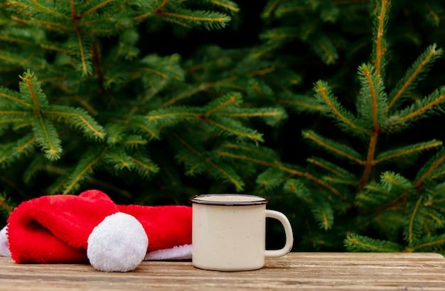 Filiżanka kawy i boże narodzenie kapelusz na drewnianym stole z gałęzi świerkowych na tle