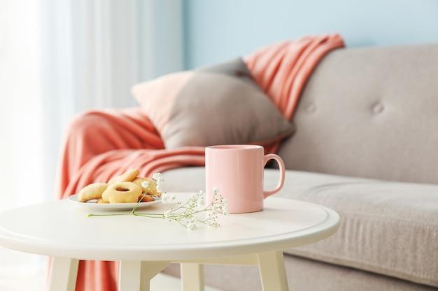 Filiżanka kawy i ciasteczka na stole w pokoju