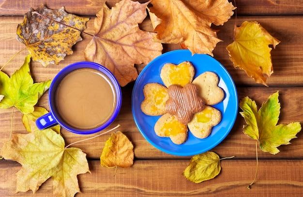Filiżanka kawy i ciasteczka na stole z suszonymi jesiennymi liśćmi. picie kawy jesienią na drewnianym stole otoczonym suchymi liśćmi jesieni