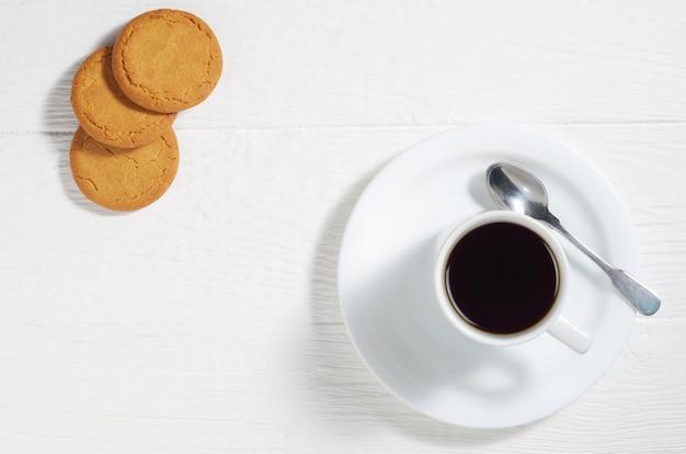 Filiżanka kawy i ciasteczka owsiane na białym drewnianym stole