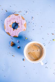 Filiżanka kawy i ciastka pączek z polewą cukrową