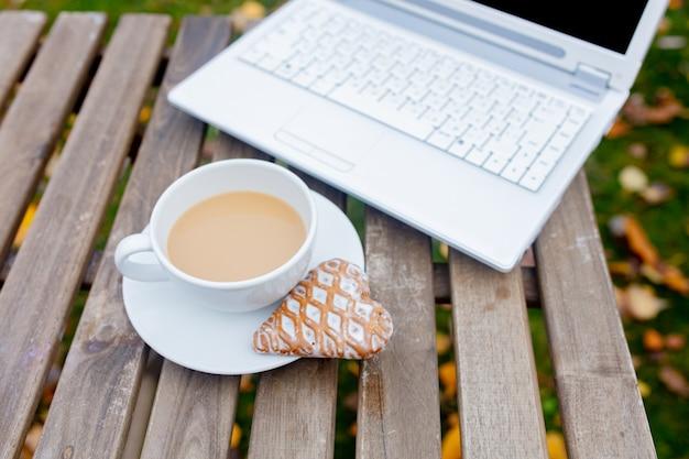 Filiżanka kawy i ciastka z laptopem