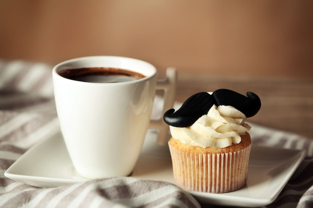 Filiżanka kawy i ciastko z wąsem na serwetka zbliżenie