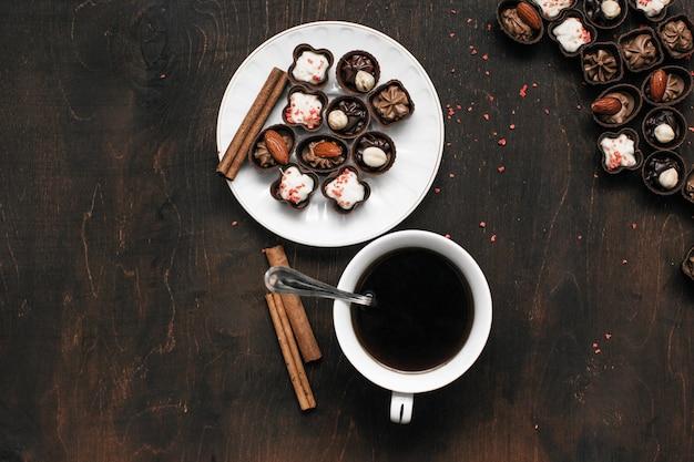Filiżanka kawy i cukierki czekoladowe na drewnianym stole