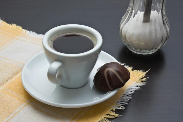 Filiżanka kawy i cukierki czekoladowe na stole