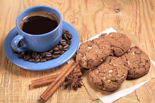 Filiżanka kawy i czekoladowe ciasteczka na śniadanie na starym drewnianym stole