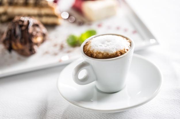 Filiżanka kawy i deser na talerzu w kawiarni cukierników lub restautant.