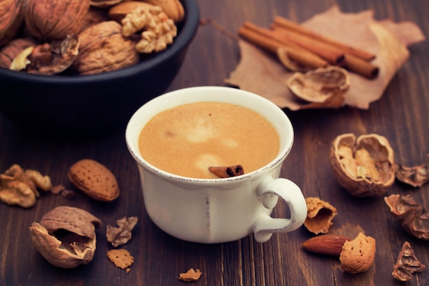 Filiżanka kawy i dokrętki na drewnianej powierzchni