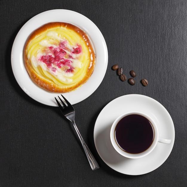 Filiżanka kawy i drożdżówka z kremem i jagodami na czarnym tle kamienia