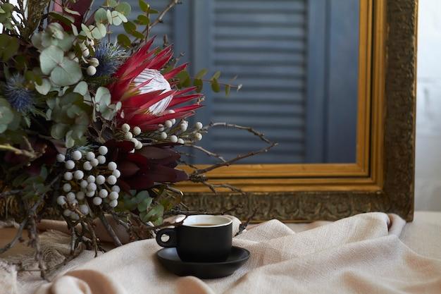 Filiżanka kawy i egzotyczny bukiet stoi na stole z beżowym lnianym obrusem na starej ramie
