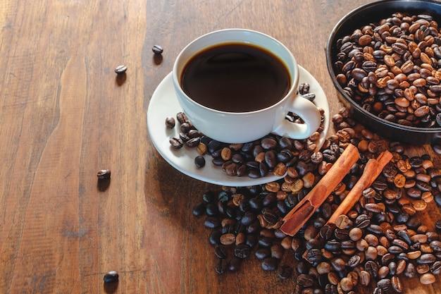 Filiżanka kawy i fasola na starym drewnianym stole