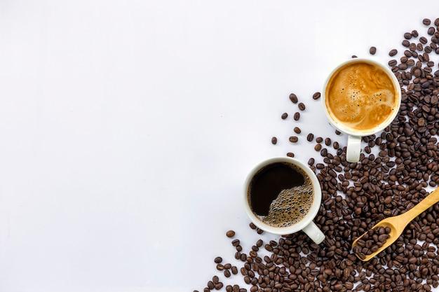 Filiżanka kawy i fasoli na białym stole
