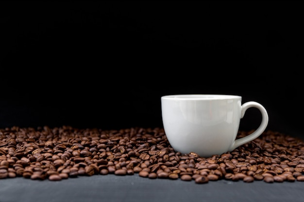 Filiżanka kawy i fasoli na czarnym drewnianym stole